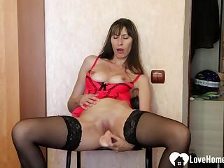 Arousing stepmom in stockings uses a dildo